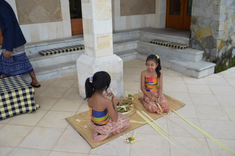 Balinese girls making flower offerings.
